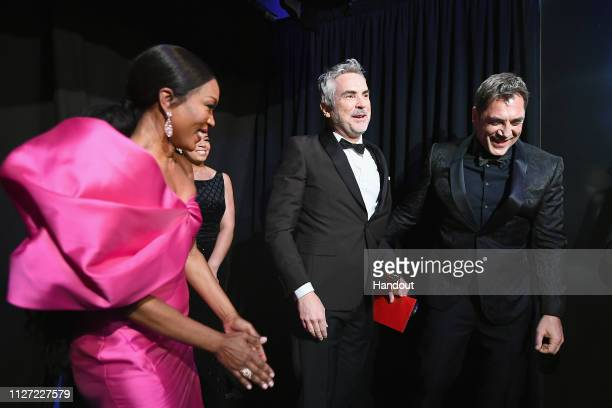 In this handout provided by AMPAS presenter Angela Bassett poses with Foreign Language Film winner Alfonso Cuaron and presenter Javier Bardem...