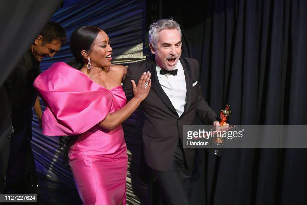 In this handout provided by AMPAS presenter Angela Bassett poses with Best Foreign Language Film winner Alfonso Cuaron backstage during the 91st...
