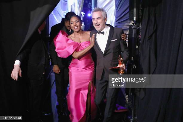In this handout provided by AMPAS presenter Angela Bassett poses with Foreign Language Film winner Alfonso Cuaron backstage during the 91st Annual...