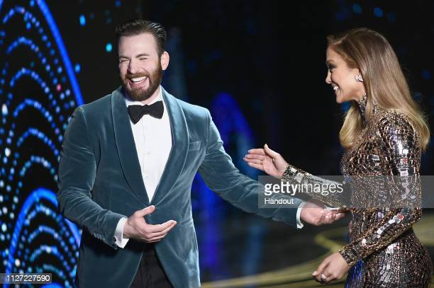 In this handout provided by AMPAS presenters Chris Evans and Jennifer Lopez speak onstage during the 91st Annual Academy Awards at the Dolby Theatre...