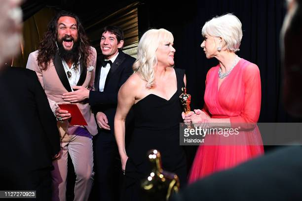 In this handout provided by AMPAS Presenters Jason Momoa and Helen Mirren pose backstage with Alex Honnold and producer Shannon Dill after winning...