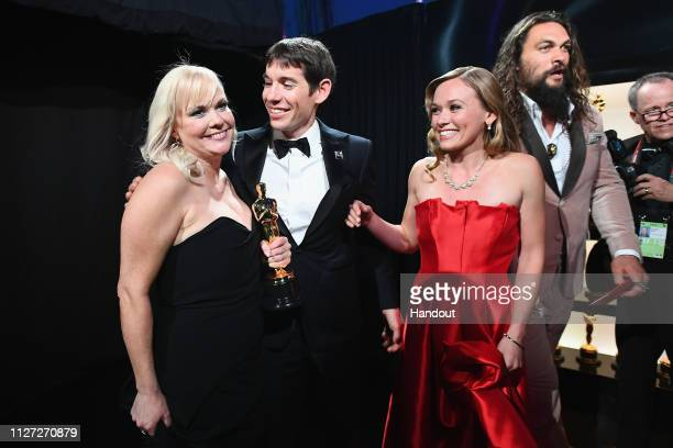 In this handout provided by AMPAS Producer Shannon Dill Alex Honnold and Sanni McCandless pose backstage after winning the Best Documentary Feature...