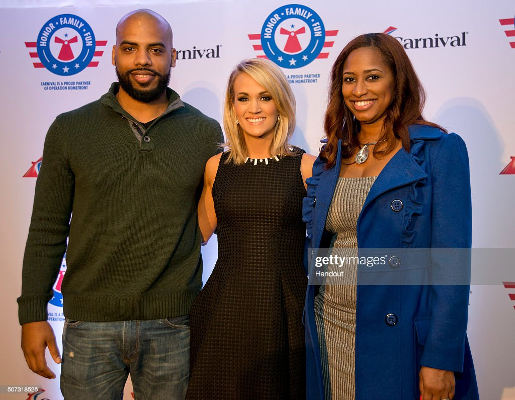 In this handout provided by Carnival Cruise Line, Carrie Underwood, center, poses with U.S. Navy Petty Officer Andrew Friedlander, left, and his wife Bryanne Friedlander, right, following a news conference Thursday, Jan. 28, 2016, in Jacksonville, Fla. The conference was staged to announce a new partnership between Underwood, Operation Homefront and Carnival Cruise Line to support U.S. military families. The effort between the three entities is to raise funds through a series of projects during Underwood's concert tour and aboard Carnival's ships as well as the company's website. FOR