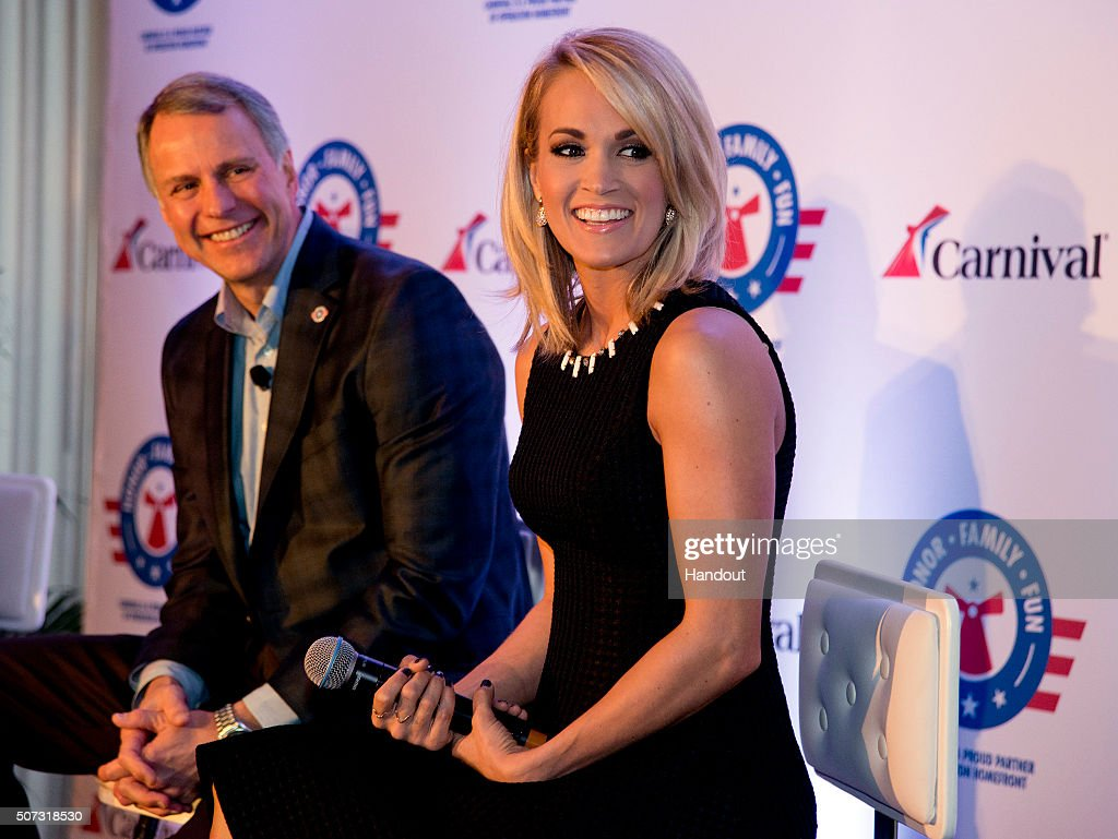 In this handout provided by Carnival Cruise Line, Carrie Underwood, right, reacts to a comment at a news conference Thursday, Jan. 28, 2016, in Jacksonville, Fla. At left is Brig. Gen. John Pray, president and CEO of Operation Homefront. Underwood, Operation Homefront and Carnival Cruise Line announced a partnership to begin a new initiative to support U.S. military families. The effort between the three entities is to raise funds through a series of projects during Underwood's concert tour and aboard Carnival's ships as well as the company's website. FOR