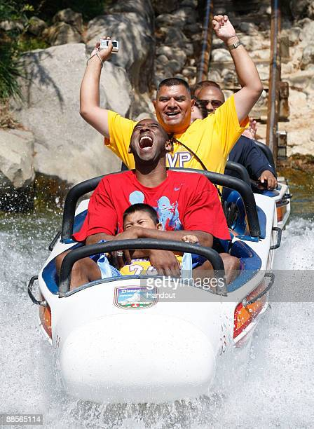 In this handout provided by Disney, Lakers star and NBA Finals MVP Kobe Bryant rides the Matterhorn Bobsleds with Jonathan Guerrero and his father...
