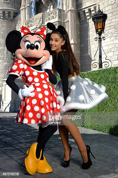 In this handout provided by Disney Parks Ariana Grande poses with Minnie Mouse during a break from taping the 'Disney Parks Unforgettable Christmas...