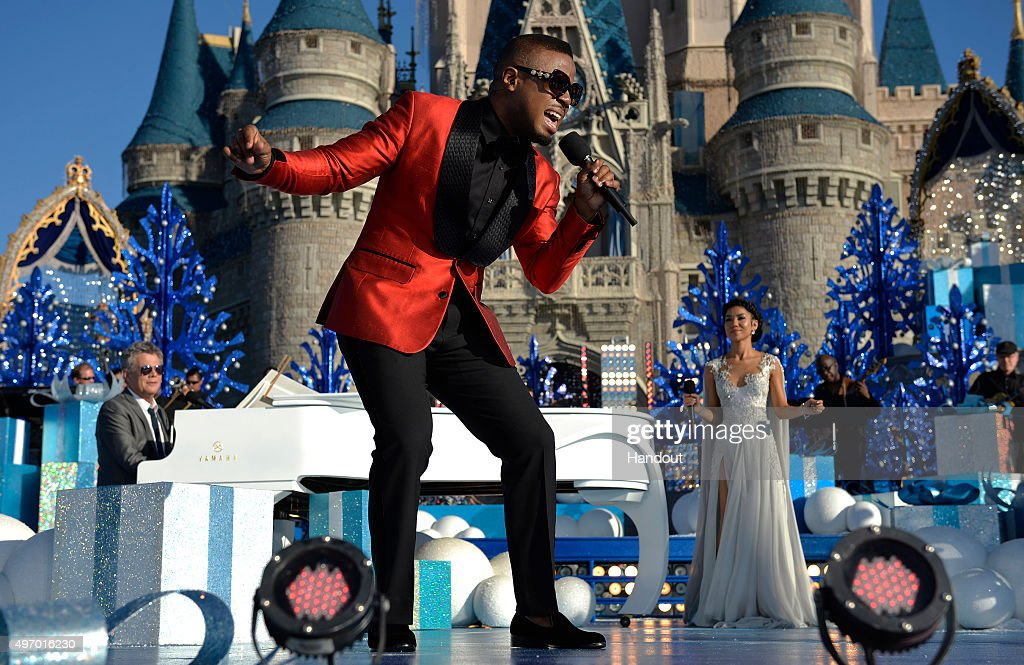 In this handout provided by Disney Parks, Charles Perry and Jhené Aiko perform during the taping of the 'Disney Parks Unforgettable Christmas Celebration' TV special in Magic Kingdom park at Walt Disney World Resort November 12, 2015 in Lake Buena Vista, Florida. The 32nd annual holiday telecast airs nationwide Dec. 25 at 10 a.m. ET and 9 a.m. CST, MST and PST on ABC-TV.