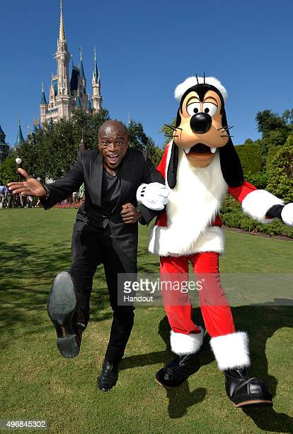 In this handout provided by Disney Parks Seal poses with Santa Goofy during a break from taping the 'Disney Parks Unforgettable Christmas...