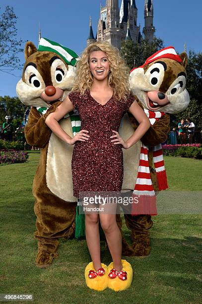 In this handout provided by Disney Parks Tori Kelly poses with Chip and Dale during a break from taping the 'Disney Parks Unforgettable Christmas...