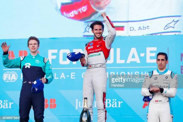 In this handout provided by FIA Formula E Daniel Abt Audi Sport ABT Schaeffler Audi etron FE04 celebrates on the podium with Oliver Turvey NIO...