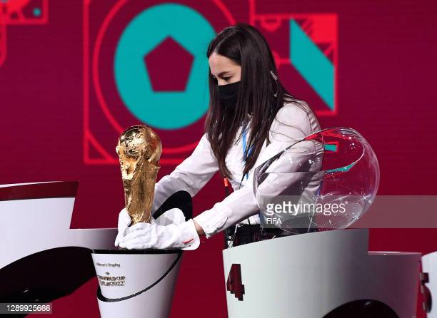 In this handout provided by FIFA A member of staff cleans the World Cup Trophy prior to the Preliminary Draw of the 2022 Qatar FIFA World Cup on...