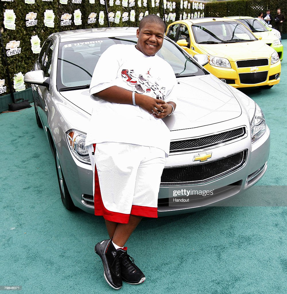 In this handout provided by General Motors, Actor Kyle Massey leans on the Chevrolet Malibu Hybrid while walking the green carpet upon his arrival at Chevy Rocks the Future, an entertainment and education event designed to inspire Los Angeles-area school children to protect the environment at The Walt Disney Studios on February 19, 2008 in Burbank, California.