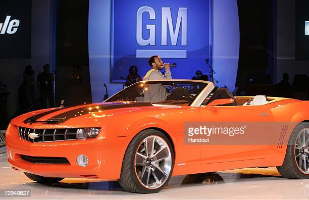 In this handout provided by General Motors musician John Legend performs on stage next to the new 2007 Chevrolet Camaro convertible concept during a...