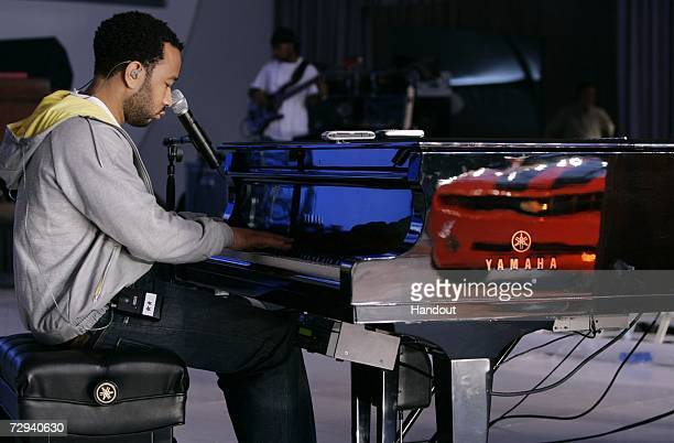 In this handout provided by General Motors musician John Legend's band performs on stage next to the 2007 Chevrolet Camaro convertible concept...