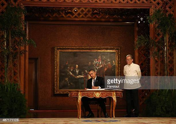 In this handout provided by Malacanang Photo Bureau' US president Barack Obama signs the palace guestbook during his twoday State visit at the...