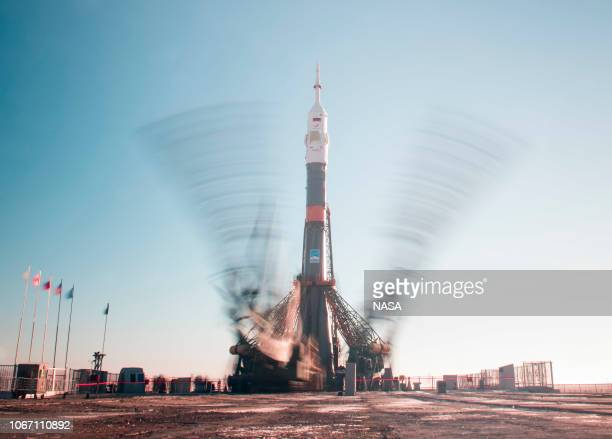 In this handout provided by NASA A long exposure is used to photograph the gantry arms raised into position to secure the Soyuz booster rocket and...