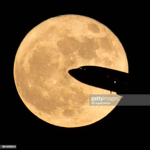 In this handout provided by NASA an aircraft taking off from Ronald Reagan National Airport is seen passing in front of the moon as it rises on...