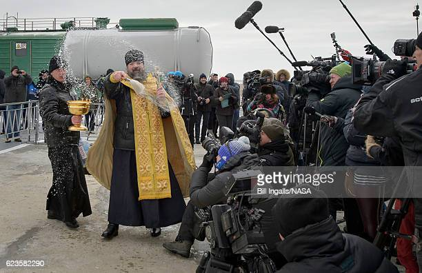 In this handout provided by NASA an Orthodox Priest blesses members of the media after he blessed the Soyuz rocket at the Baikonur Cosmodrome Launch...