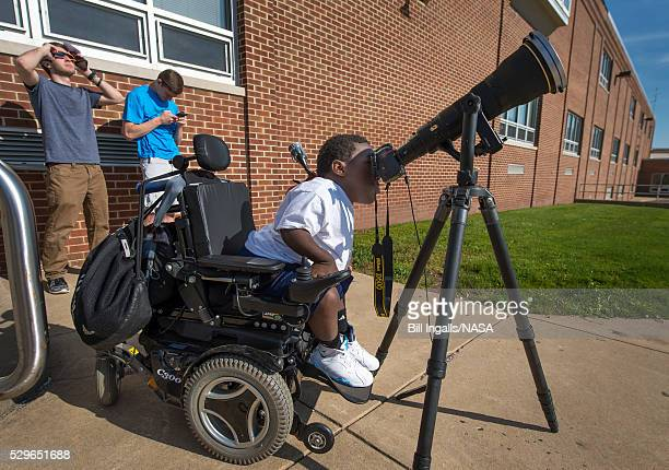 In this handout provided by NASA Boyertown Area High School 12th grade student Jay Hallman looks through a photographers lens and solar filter to see...