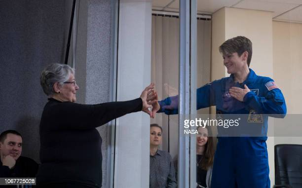 In this handout provided by NASA Expedition 58 Flight Engineer Anne McClain of NASA who is in quarantine puts her hand up to the glass to meet her...