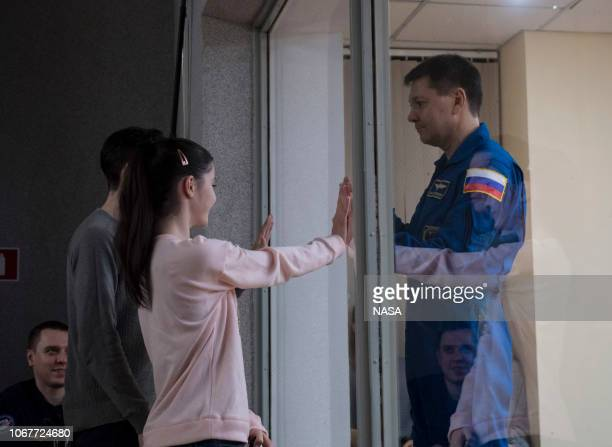 In this handout provided by NASA Expedition 58 Soyuz Commander Oleg Kononenko of Roscosmos right who is in quarantine puts his hands up to the glass...
