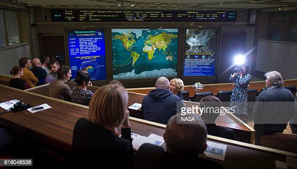In this handout provided by NASA friends and family members of the Soyuz MS02 crew watch a live view of the International Space Station as seen by...