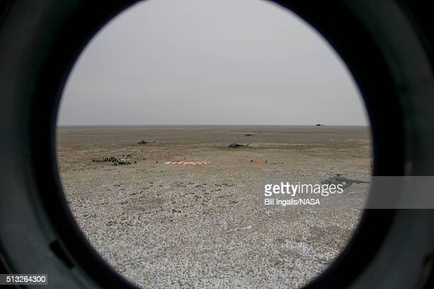 In this handout provided by NASA The Soyuz TMA18M spacecraft landing site is seen through the window of an arriving Russian MI8 helicopter after...