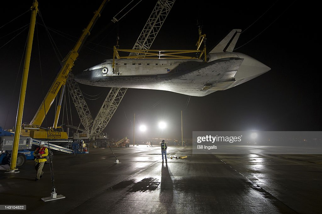 In this handout provided by NASA, the space shuttle Discovery is suspended from a sling held by two cranes shortly after the NASA 747 Shuttle Carrier Aircraft (SCA) was pushed back from underneath at Washington Dulles International Airport on April 19, 2012, in Sterling, Virginia. Discovery, the first orbiter retired from NASA's shuttle fleet, completed 39 missions, spent 365 days in space, orbited the Earth 5,830 times, and traveled 148,221,675 miles. NASA will transfer Discovery to the National Air and Space Museum to begin its new mission to commemorate past achievements in space and to educate and inspire future generations of explorers.