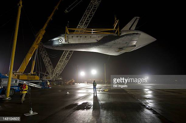 In this handout provided by NASA the space shuttle Discovery is suspended from a sling held by two cranes shortly after the NASA 747 Shuttle Carrier...