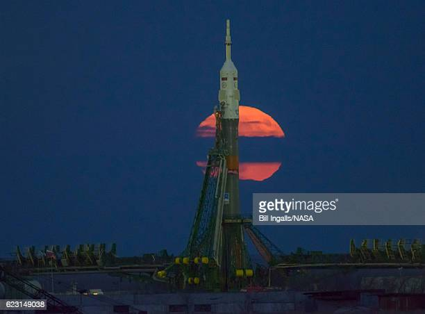 In this handout provided by NASA The supermoon is seen rising behind the Soyuz rocket at the Baikonur Cosmodrome launch pad on November 14 2016 in...