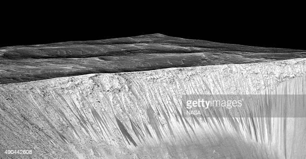 In this handout provided by NASA's Mars Reconnaissance Orbiter dark narrow streaks on the slopes of Garni Crater are inferred to be formed by...