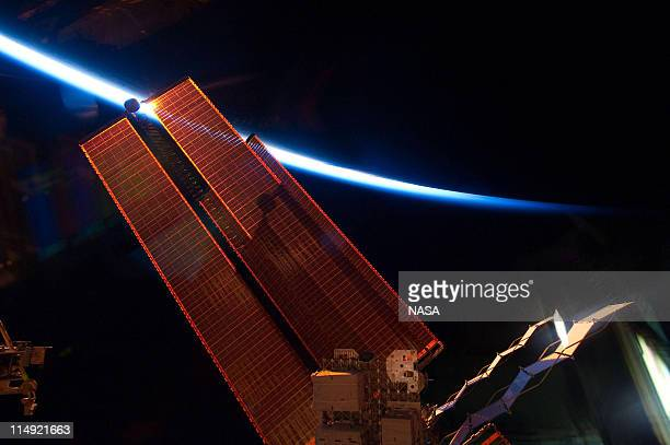 In this handout provided by National Aeronautics and Space Administration International Space Station solar array wings intersect the thin line of...