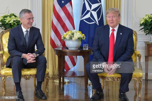 In this handout provided by NATO, Jens Stoltenberg, Secretary General of NATO speaks with U.S. President Donald Trump ahead of the NATO Leaders...