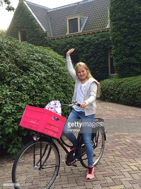 In this handout provided by Netherlands Government Information Service Crown Princess Amalia of The Netherlands waves on her first day of attending...