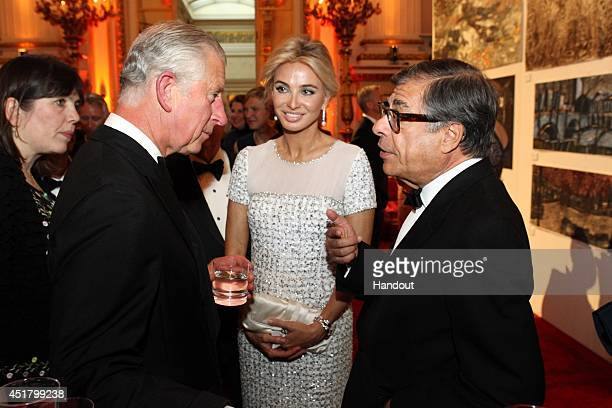 In this handout provided by Paul Burns Prince Charles Prince of Wales greets Corinna zu SaynWittgenstein and Bob Colacello at a fund raising event he...