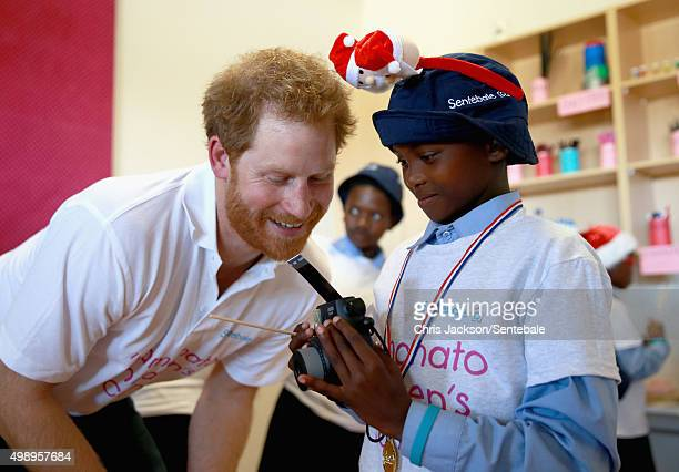 In this handout provided by Sentebale Prince Harry helps a young boy use a Fuji Instax camera during a photography activity at the new Mamohato...