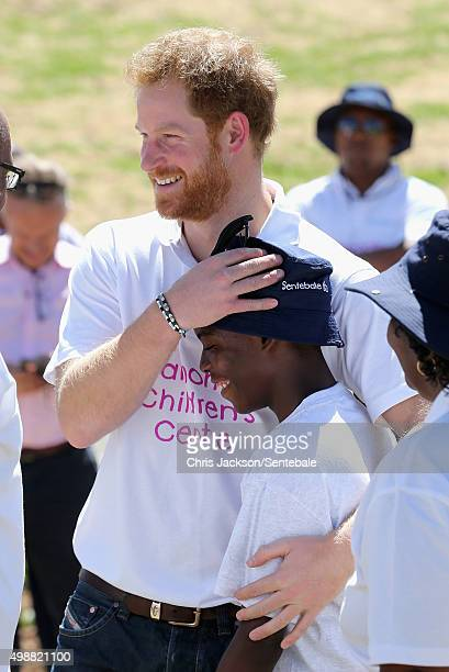 In this handout provided by Sentebale Prince Harry hugs 'Mutso' a young boy he made friends with on his first visit to Lesotho at the Official...