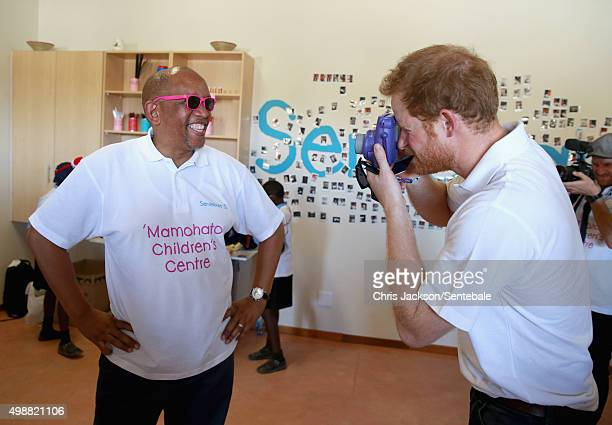 In this handout provided by Sentebale, Prince Harry takes a photograph of Prince Seeiso using a Fuji Instax camera during a photography activity at...