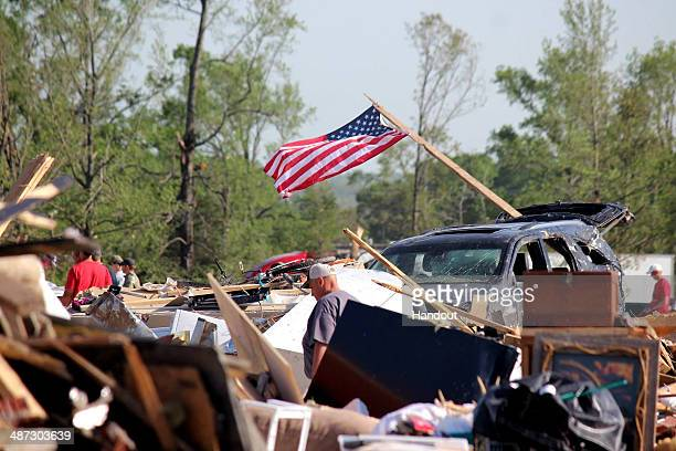 In this handout provided by the Arkansas National Guard people walk amongst the rubble following a deadly tornado April 28 2014 in Vilonia Arkansas...
