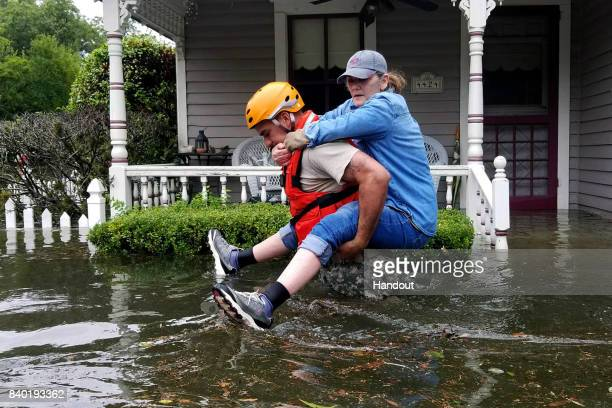 In this handout provided by the Army National Guard A Texas National Guardsman carries a resident from her flooded home following Hurricane Harvey...