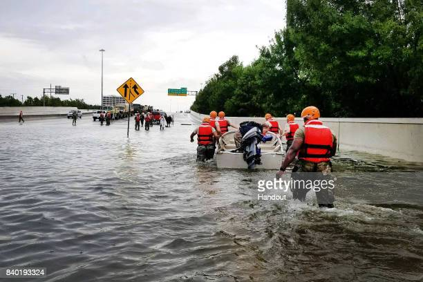In this handout provided by the Army National Guard Texas National Guardsmen rescue a resident by boat during flooding caused by Hurricane...
