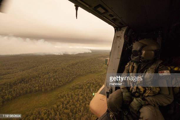 In this handout provided by the Australian Department of Defence, A Royal Australian Navy MRH-90 helicopter crew member, observes the fires on...