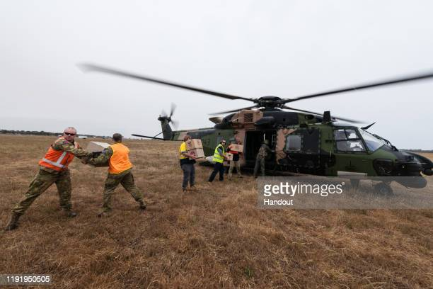In this handout provided by the Australian Department of Defence, A Royal Australian Navy MRH-90 helicopter is loaded with food and water by soldiers...
