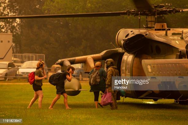 In this handout provided by the Australian Department of Defence an Australian Army Soldier helps people evacuate onto a Blackhawk helicopter at Omeo...