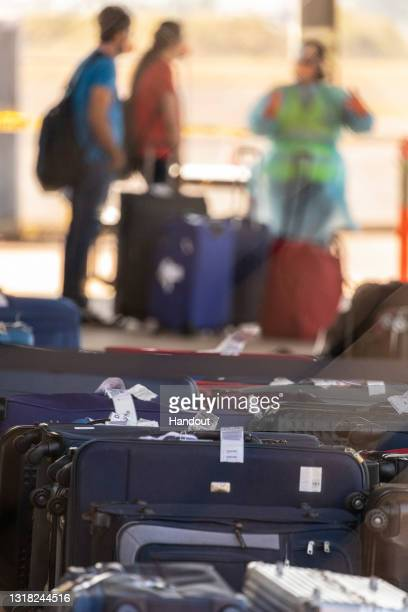 In this handout provided by the Australian Department of Defence, expatriates collect luggage from their Delhi flight after arriving at RAAF Base...