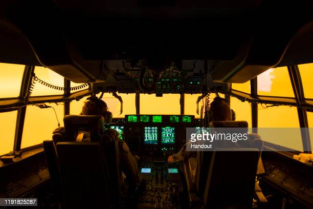 In this handout provided by the Australian Department of Defence the flight deck is lit by the red glow of the fires as the aircrew of a C130J...