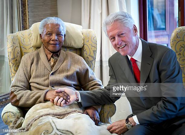 In this handout provided by the Clinton Foundation former US President Bill Clinton poses with former South African President Nelson Mandela on the...