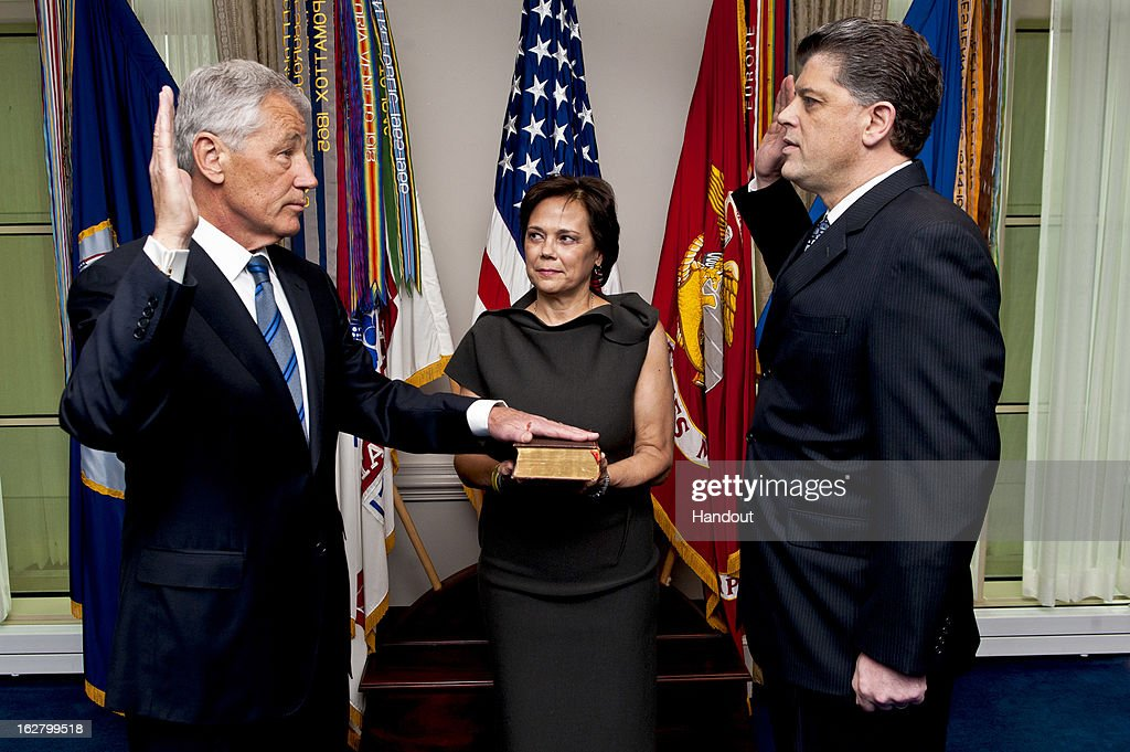 In this handout provided by the Department of Defense, as his wife Lilibet holds the bible, Chuck Hagel (L) is sworn into office as the 24th Secretary of Defense by Michael L. Rhodes, DoD Director of Administration and Management at the Pentagon February 27, 2013 in Arlington, Virginia. After a tumultuous confirmation hearing in the Senate, Hagel was sworn in during a small private ceremony on his first day at the Department of Defense.