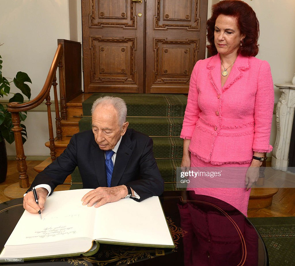 In this handout provided by the GPO, Israeli President Shimon Peres signs the book at Latvia Parliament on July 30, 2013 in Riga, Latvia. Shimon Peres has embarked on a state visit to Latvia and Lithuania.