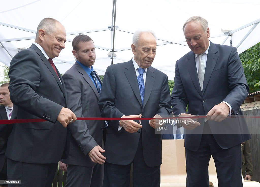In this handout provided by the GPO, Israeli President Shimon Peres (2nd-R) helps Latvia President Andris Berzinns (R) cut the ribbon at the opening of the Zanis Lipke Memorial Museum on July 30, 2013 in Riga, Latvia. Shimon Peres has embarked on a state visit to Latvia and Lithuania.